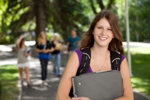 Portrait of a relaxed high school girl with binder